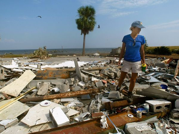 A woman viewing her house after a hurricane